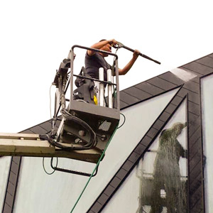 Een werknemer reinigt een pand met een hogedrukspuit, het is een werknemer van Joyfull Onderhoud, een bedrijf werkzaam in vastgoedonderhoud.